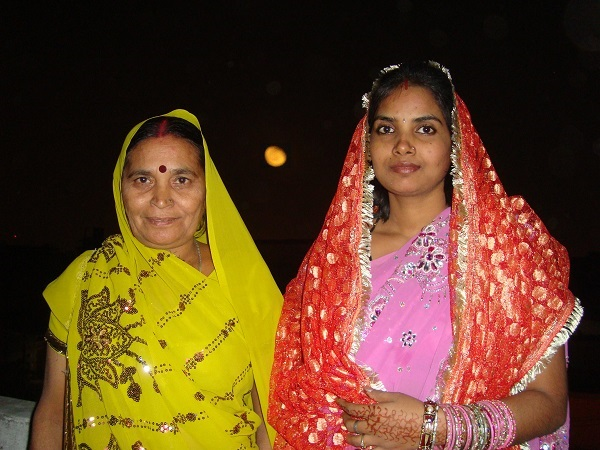 Two Indian women dressed in Indian attire to celebrate Karva Chauth. Full moon is showing in the sky in background.