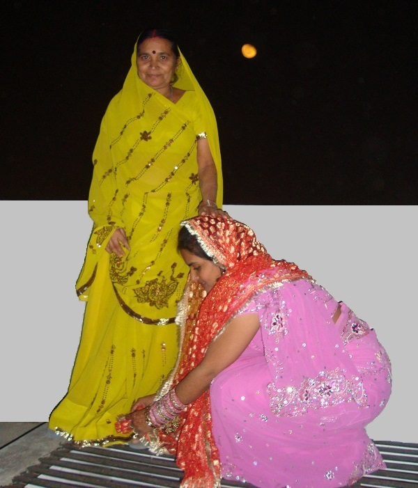 Married woman touching the feet of her mother-in-law to take blessings on Karva Chauth.